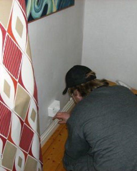 En av Bottnia IT:s anställda monterar dosa (konverter) inomhus.